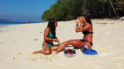 Pretty smiling ladies on vacation spending quality time at the beach on paradise white sand and blue