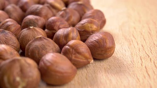 Hazelnut kernels are stacked on a wooden textured board