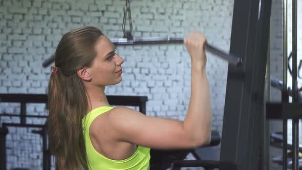 Thumbnail for Attractive Athletic Woman Exercising on Lat Pulldown Cable Gym Machine