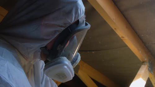 Man in Respirator Mask Making Thermal Roof Insulation