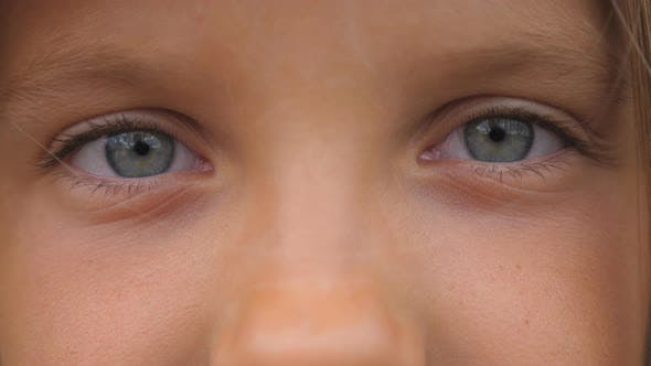 Thumbnail for Blue Eyes of Beautiful Small Girl Blinking and Looking Into Camera with a Sad Sight. Portrait of