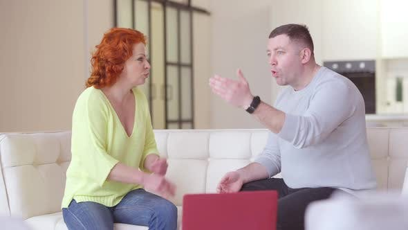Annoyed Adult Caucasian Couple Arguing in Living Room Sitting on Couch