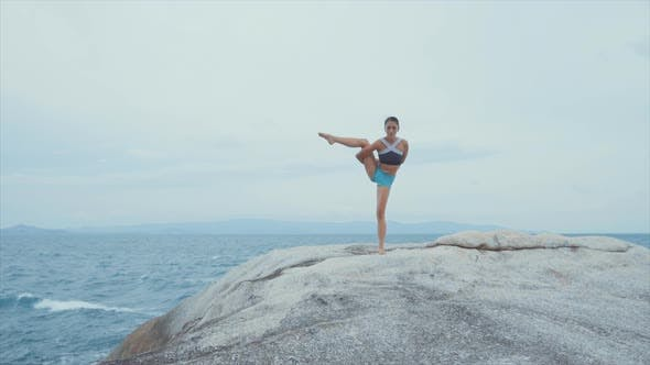 Thumbnail for Woman Standing on One Leg and Meditating on Rocks Near Ocean