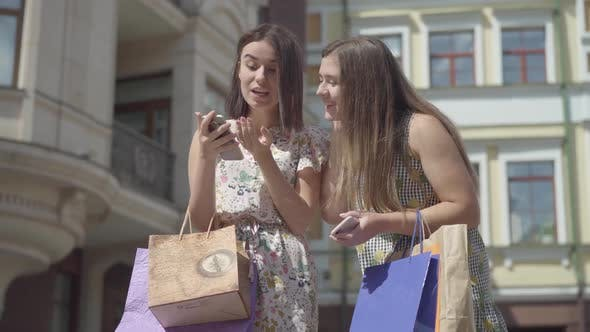Thumbnail for Two Happy Girlfriends After Shopping with Shopping Bags Texting on the Cellphone in Front