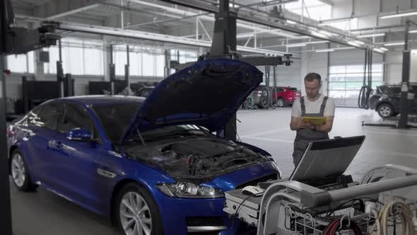 Thumbnail for Mature Male Mechanic Making Notes and Using Computer While Repairing a Car