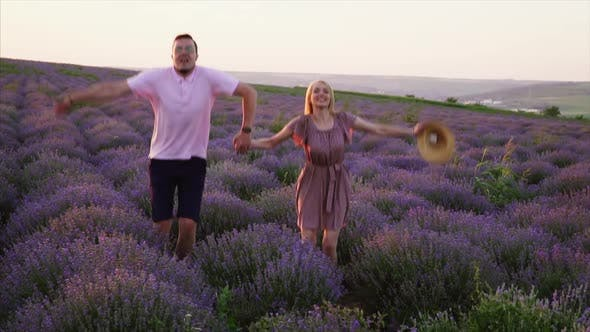 Young Couple Jumping Up in Flowering Lavender Field, Slow Motion