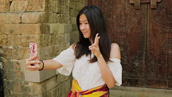 Thumbnail for Teenage Chinese tourist explores a temple in Bali.