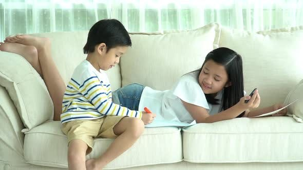 Asian Children Drawing Together In Living Room