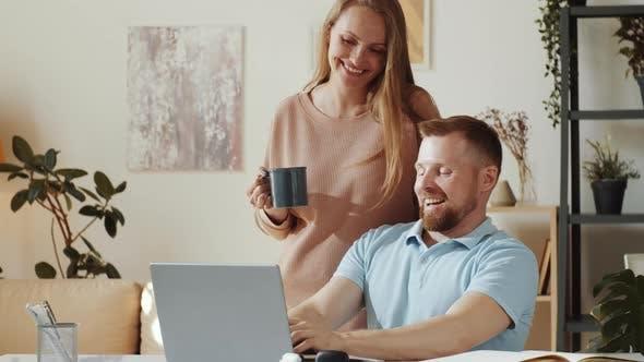 Fröhlicher Mann mit Laptop und Chat mit Frau zu Hause