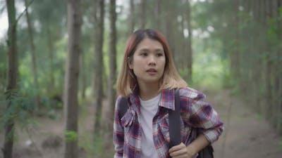 Hiker Asian backpacker woman on hiking adventure feeling freedom walking in forest.