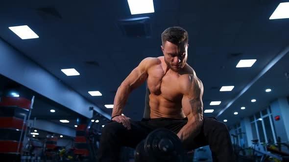 Hübscher Power Athletic Man Bodybuilder macht Übungen mit Hanteln