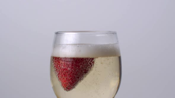Thumbnail for Strawberry Falling Into a Glass of Champagne on a White Background. Slow Motion 1080p