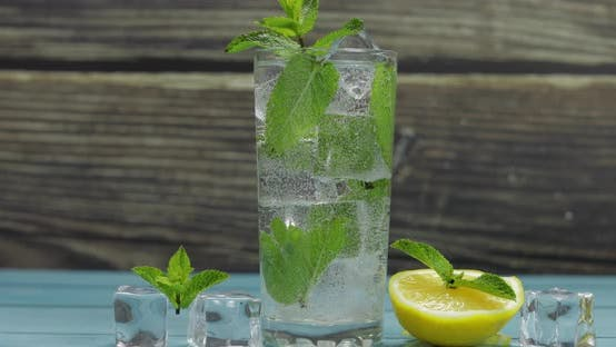 Clear Water in Glass with Green Mint Leaves and Ice Cubes