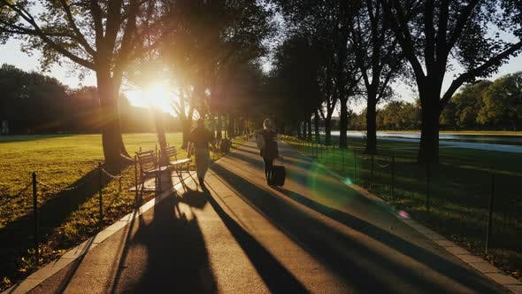 Cover Image for A Woman with a Travel Bag Goes Forward Along a Long Path at Sunset. Washington, the National Mall