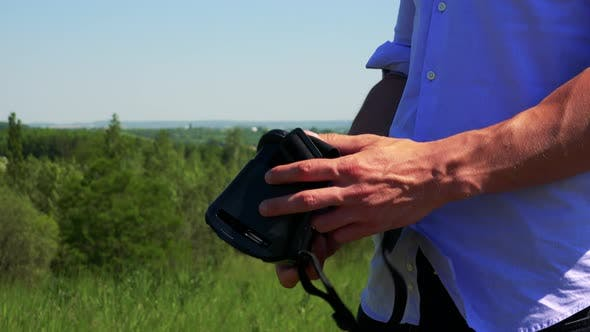 Thumbnail for Young Handsome Man Examines Virtual Reality Glasses - Countryside in the Background - Closeup