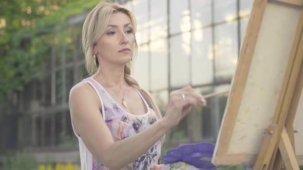 Thumbnail for Portrait of Confident Charming Blond Woman with Brown Eyes Painting Landscape Outdoors