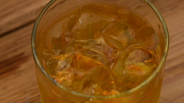 Thumbnail for Ice cubes fall in glass of whiskey on bar counter