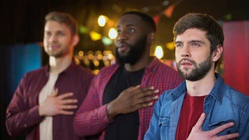 Multiracial Friends Singing National Anthem Before Football Game Beginning, Pub