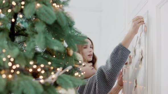 Thumbnail for Smiling Woman Hugging Girl Near Christmas Tree in Living Room.