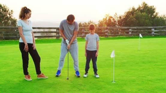 Thumbnail for Glückliche Eltern mit jungen Sohn genießen Zeit zusammen üben mit Golf Club.