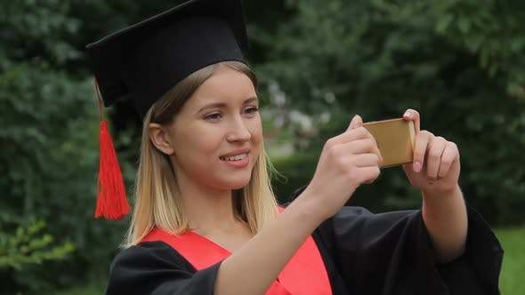 Cover Image for Beautiful Girl in Academic Dress Filming Friends on Smartphone, Happy Graduation