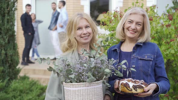 Thumbnail for Two Caucasian Mature Women Smiling and Holding a Cake and a Bucket of Flowers