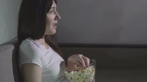 Young Woman Alone Watching a Movie in the Evening with Popcorn