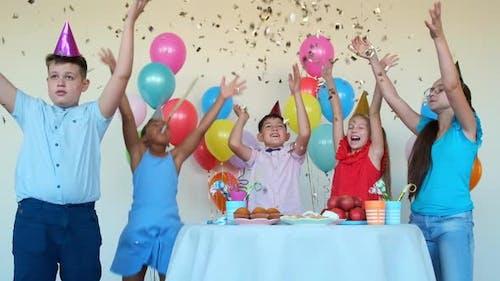 Kinder werfen glänzende Konfetti feiern Geburtstag am Tisch
