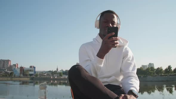 Thumbnail for Black Man Scrolling On His Phone Outdoors