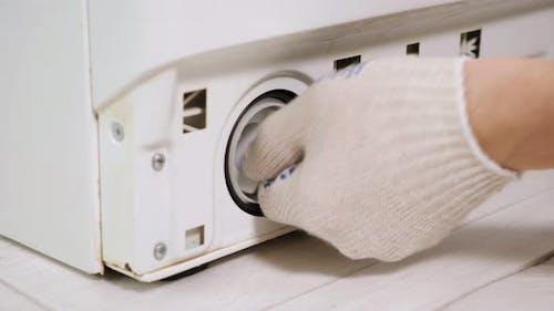 Serviceman in Gloves Takes Pump Filter Off Washing Machine