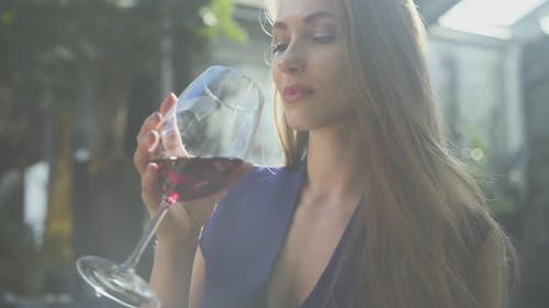 Pretty Elegant Woman with Long Hair Drinking Red Wine From the High Glass in Soft Light. The Lady Is