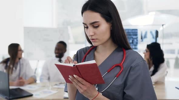 Thumbnail for Female Doctor Making Some Note in the Notebook