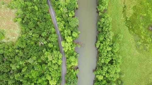 Flight with drone over a road around a river