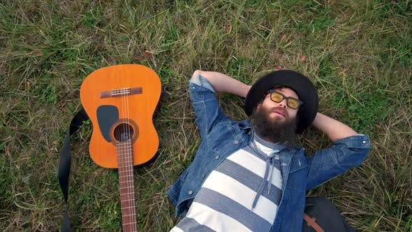 Thumbnail for Modern Young Man Lying on Grass and Holding Acoustic Guitar. Top View