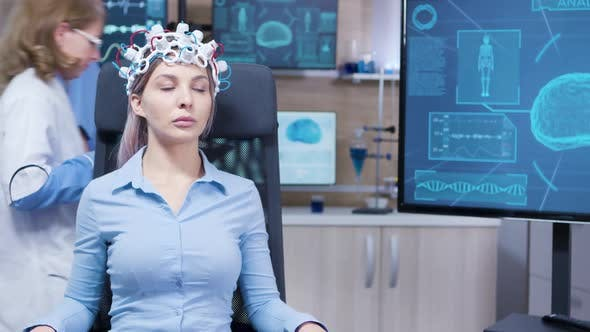 Female Sitting on a Chair with Brainwaves Scaner Headset