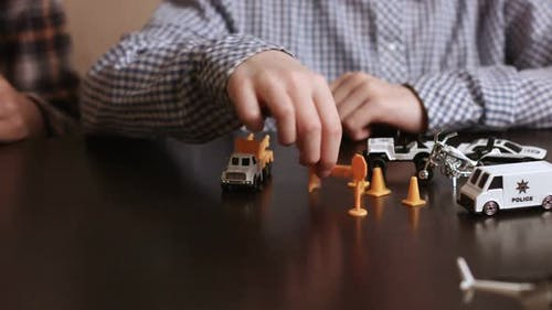 Boy's Hand Moves Toy Vehicle.