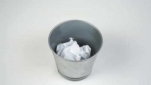 Jetant une feuille de boule de papier froissée dans une poubelle