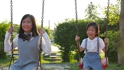 Asian Girl And Her Brother Playing Swing Together In The Park Slow Motion