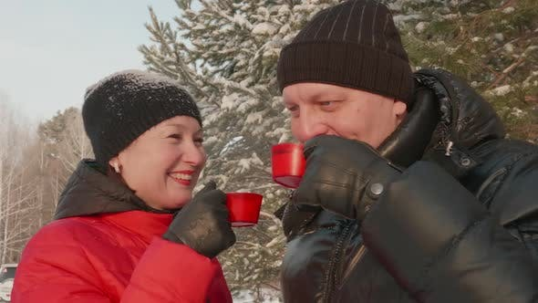 Thumbnail for Happy Couple Drinking Hot Tea While Winter Walk in Snowy Forest Close Up