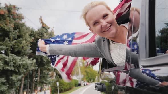 Thumbnail for Happy Middle-aged Woman with an American Flag. Looks Out the Window of a Moving Car