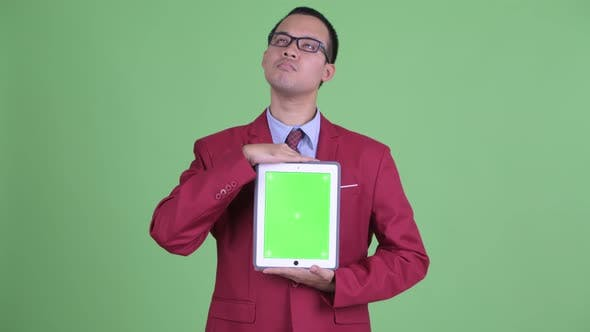 Thumbnail for Happy Asian Businessman Thinking While Showing Digital Tablet