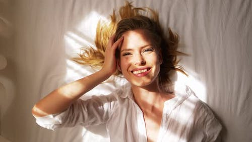 Blonde Female Waking Up While Lying on Bed with Sun Beaming on Her