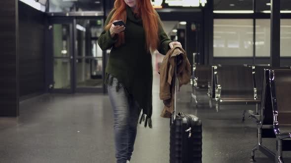 Junge Frau geht durch ein Flughafenterminal und nutzt Smartphone