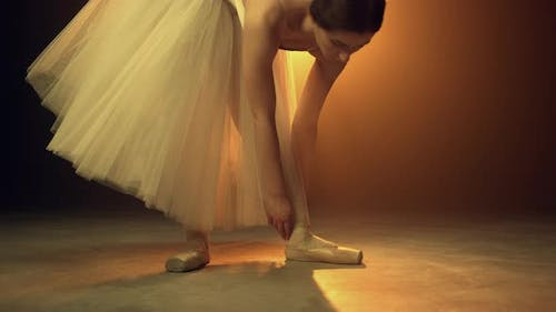Young Dancer Putting on Ballet Shoes Indoors