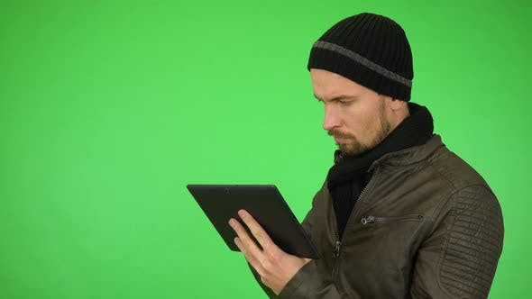 Cover Image for A Young Man in a Winter Outfit Works on a Tablet, Then Smiles at the Camera - Green Screen Studio