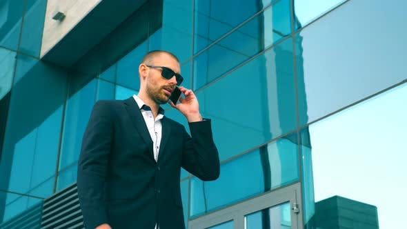 Thumbnail for Businessman in Sunglasses Walking Near Office and Talking on Phone. Young Happy Business Man Going