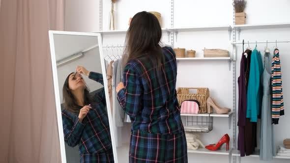 Frau im Pyjama Färbt Wimpern im Kleiderschrank