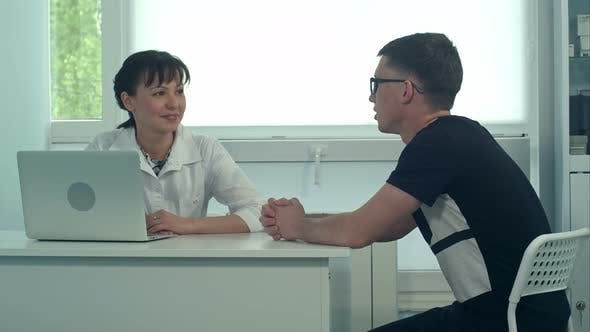 Thumbnail for Smiling Female Doctor Listening To Male Patient in Her Office