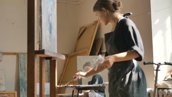 Thumbnail for Frau zeichnet Bild mit Pinsel in der Nähe von Paletten und Spiegel