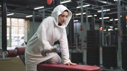 Muslimische Frau in Hijab für Sportübungen mit Hanteln im Fitnessstudio Frau mit Fokus auf Training